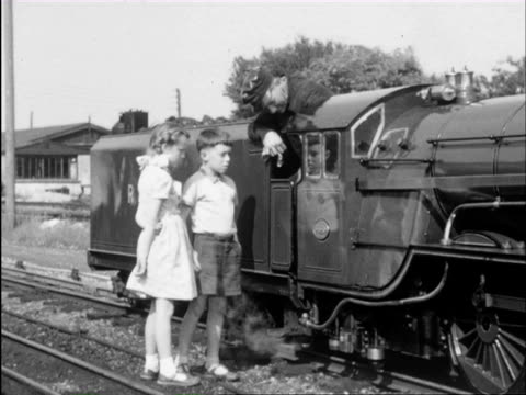 MS Miniature railway full of passengers and girls and boys waving and smiling to camera/ Fairbourne, Sutton, Romney, Hy and Dymchurch, Gwynedd, London, Kent, Wales, England