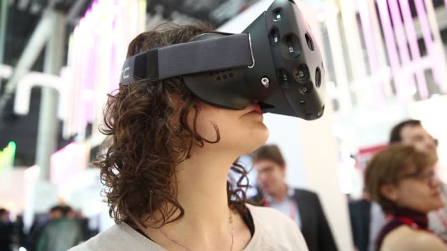 Miniature sensors sit on an HTC Vibe VR virtual reality headset in the HTC Corp pavilion An employee holds an HTC Vibe VR virtual reality headset in...