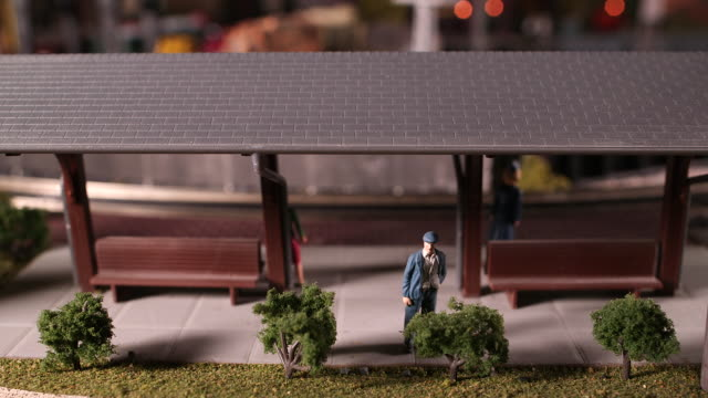 Miniature train station with man waiting for model train