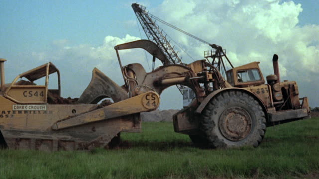 1979 MONTAGE Mining equipment stripping soil and rocks / trucks hauling and dumping rocks / Yorkshire, England, United Kingdom