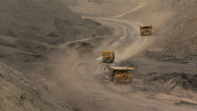 mining trucks at a coal mine - miniera video stock e b–roll