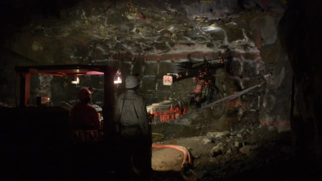 a mining vehicle illuminates the rock face inside the northam platinum ltd booysendal platinum mine located outside the town of lydenburg in... - miniera video stock e b–roll