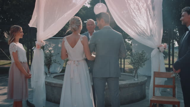 minister reading vows to couple in wedding ceremony - best man stock videos and b-roll footage