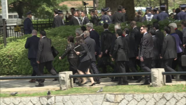 G7 ministers and accompanying security staffs walking toward Atomic Bomb Dome as the Secretary of State John Kerry suggested earlier during the event