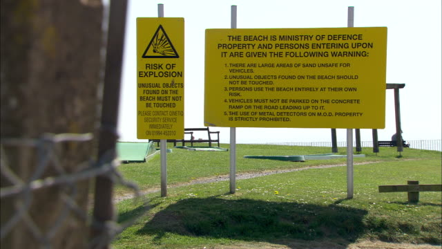 stockvideo's en b-roll-footage met a 'ministry of defence' sign warns of explosions near a beach in south wales. - ministerie van defensie