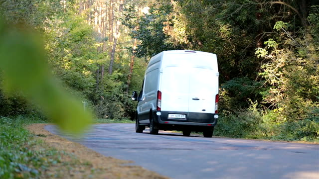 minivan drives along the forest road. - van stock videos & royalty-free footage