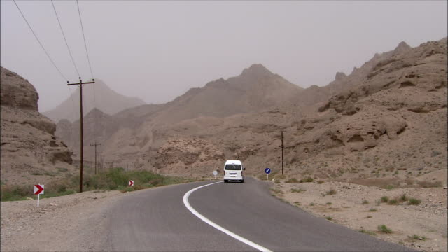 WS PAN Minivan driving along desert highway, Iran