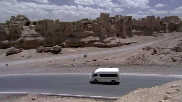 WS HA PAN Minivan driving past mud village, Iran