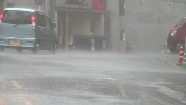 a minivan moves through heavy rain on a city street. - van stock videos & royalty-free footage
