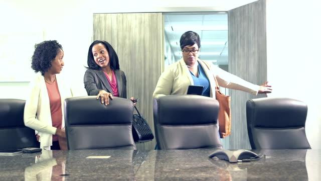 Minority businesswomen enter board room for meeting