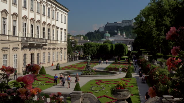 mirabell palace and mirabell gardens against salzburg cathedral and fortress hohensalzburg, salzburg, austria - 社会史点の映像素材/bロール