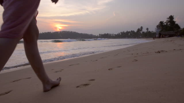 mirissa beach, feet of a tourist walking along the beach at sunset, south coast of sri lanka, asia  - sri lanka stock videos and b-roll footage