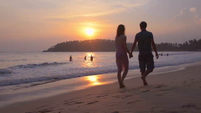 mirissa beach, tourist couple on a romantic walk along the beach at sunset, south coast of sri lanka, asia  - sri lanka stock videos & royalty-free footage