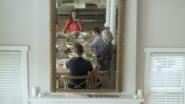 Mirror image of family dining together, making a toast.