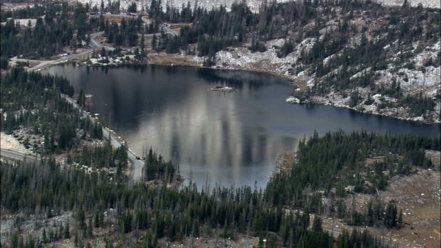 mirror lake at foot of snowy range mountain, medicine bow national forest - aerial view - wyoming, albany county, united states - national forest stock videos and b-roll footage
