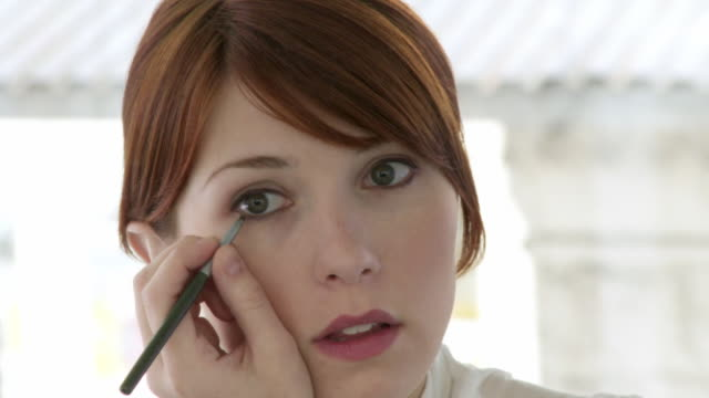 cu, mirror reflection of young woman applying make-up - make up stock videos and b-roll footage