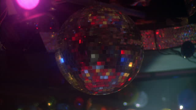 a mirrored ball reflects disco lights. - disco lights stock videos & royalty-free footage
