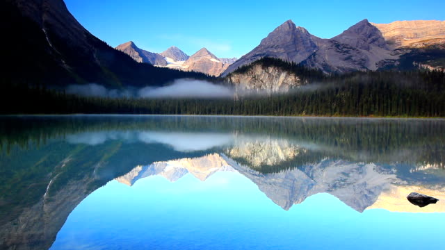 mirrored image of mountains on lake surface - british columbia stock videos & royalty-free footage