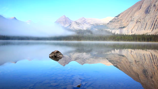 mirrored image of mountains on lake surface with mist rising - coastline stock videos & royalty-free footage