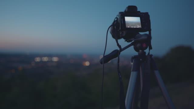 mirrorless camera being used to shoot a timelapse of a distant city at night - digital spegelreflexkamera bildbanksvideor och videomaterial från bakom kulisserna
