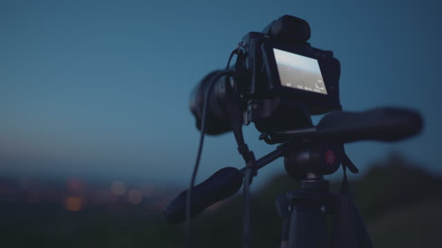 mirrorless camera being used to shoot a timelapse of a distant city at night - photography stock videos & royalty-free footage