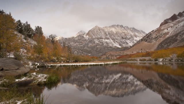 mirror-like north lake reflects the eastern sierra mountains and autumn trees. - californian sierra nevada stock videos & royalty-free footage