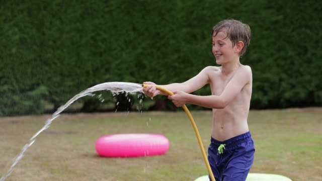 mischievous boy spraying water - exhilaration stock videos & royalty-free footage