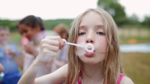 mischievous girl blowing bubbles - bubble wand stock videos & royalty-free footage