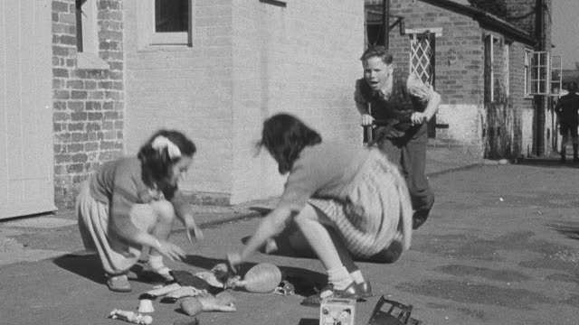 1950 montage mischievous orphan rolling compactor between two playing orphans and smashing their toys / united kingdom - orphan stock videos & royalty-free footage