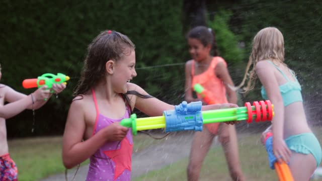 mischievous water gun fight! - swimwear stock videos & royalty-free footage