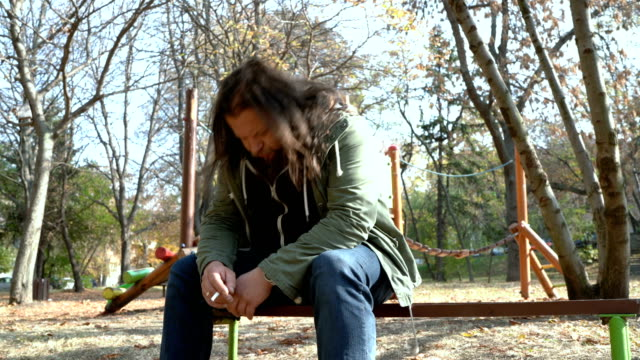 miserable looking male sitting alone in the park - restlessness stock videos and b-roll footage