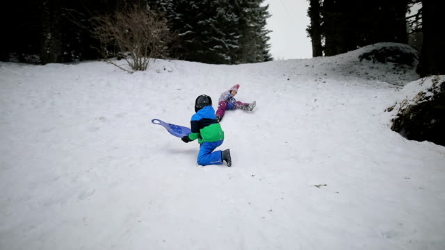 vidéos et rushes de misfortune.kids ayant monté sur la neige trop vite et s'écraser tout en sledding - trébucher