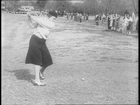 miss goldthwaite surrounded by spectators hits a gold ball / the spectators turn to watch the ball's progress / betty jameison hits a golf ball /... - golf swing women stock videos & royalty-free footage