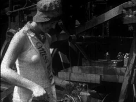 b/w 1926 miss miami wearing swimsuit + conductor hat oiling train / newsreel - 1926 stock videos & royalty-free footage