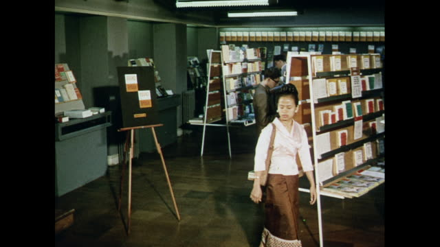 vídeos de stock, filmes e b-roll de montage miss vatsana, a law student from laos visits a books from britain exhibition held in a london bookshop. - livraria