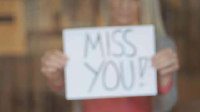 miss you sign during airborne illness crisis mature female shelter at home during quarantine handheld signs 4k video series - prevenzione delle malattie video stock e b–roll