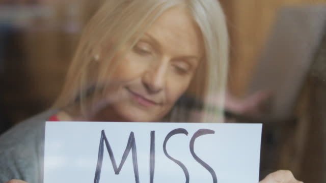 miss you sign during airborne illness crisis mature female shelter at home during quarantine handheld signs 4k video series - holding stock videos & royalty-free footage
