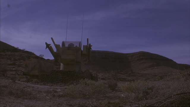 A missile launcher in the desert explodes and burns.