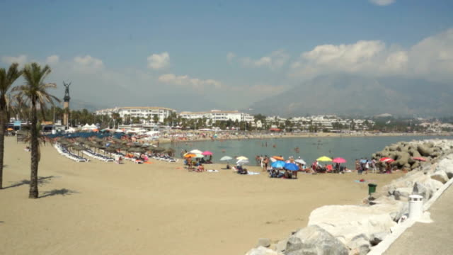 European arrest warrant issued for parents SPAIN Marbella EXT Wide shot people on sandy beach PAN