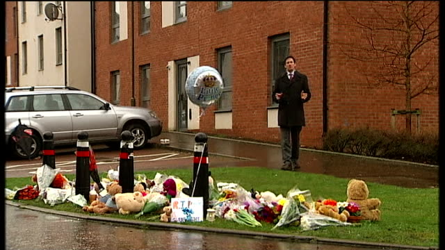body found / neighbours attend church service Vox pop Floral tributes and cuddly toys lying on ground Reporter to camera Close shot floral tributes...