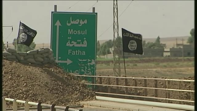 missing bradford families believed to be in syria: one mother gets in touch; lib iraq: ext road sign to 'mosul' with islamic state flags beside... - militante gruppe stock-videos und b-roll-filmmaterial