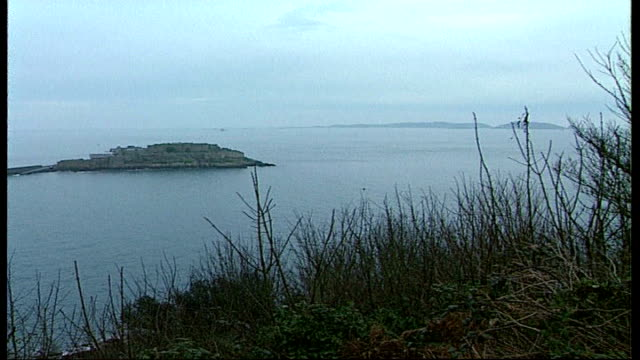 missing diver admits he secretly returned to dry land; tx 6.8.2006 channel islands: guernsey: ext general view of coastline dissolve to - guernsey stock videos & royalty-free footage