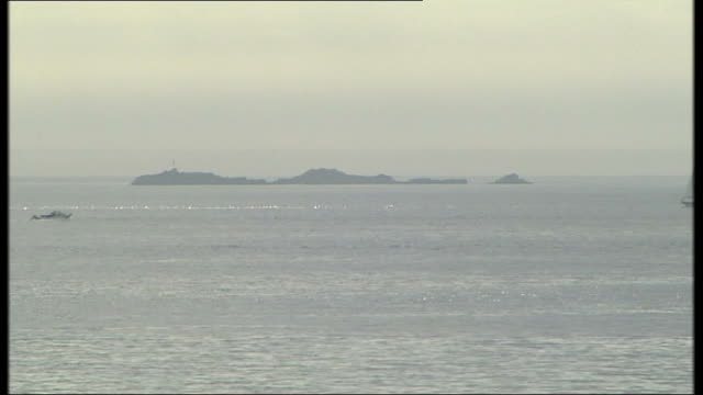 missing diver found alive; channel islands: guernsey: ext long shot island of guensey seen across water dan harvey tearfully hugging his son's... - guernsey stock videos & royalty-free footage
