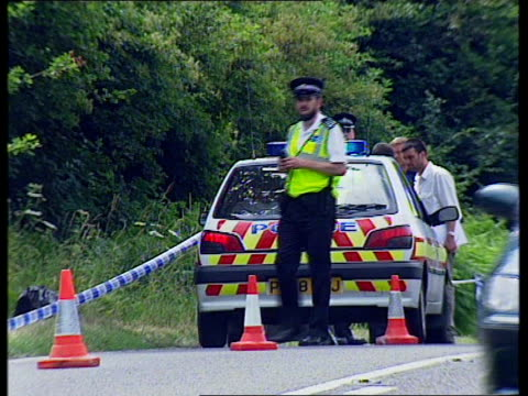 vídeos de stock e filmes b-roll de police search scene after body found england west sussex ext helicopter overhead / police searching along main road / police vans parked / traffic... - encontrar