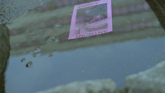 CU Missing poster floating in puddle as it rains/ Berlin, Germany