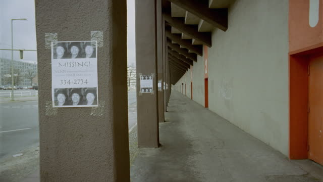 ws missing poster superimposed over row of columns on outside of building/ berlin, germany - missing persons stock videos & royalty-free footage