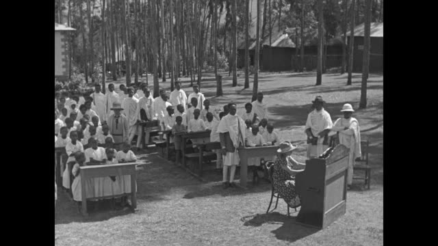 missionary school children sing outside with organ accompaniment / close up of children / note: exact day not known - missionary stock videos & royalty-free footage