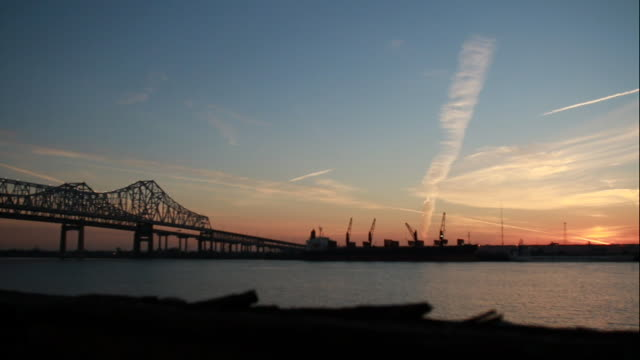 mississippi river, crescent city connection twin cantilever bridges left, pink clouds in sky, bird flying, pier across frame fg, construction cranes... - cantilever bridge stock videos & royalty-free footage