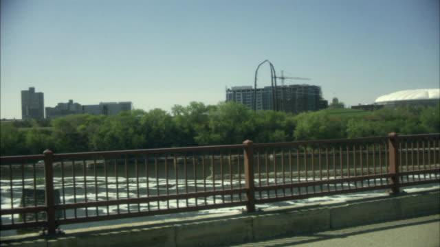 ws mississippi river/ pan people walking over stone arch bridge with skyline in background/ minneapolis, minnesota - okänt kön bildbanksvideor och videomaterial från bakom kulisserna