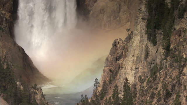 Mist and spray generates rainbow under Lower Falls, Yellowstone, USA